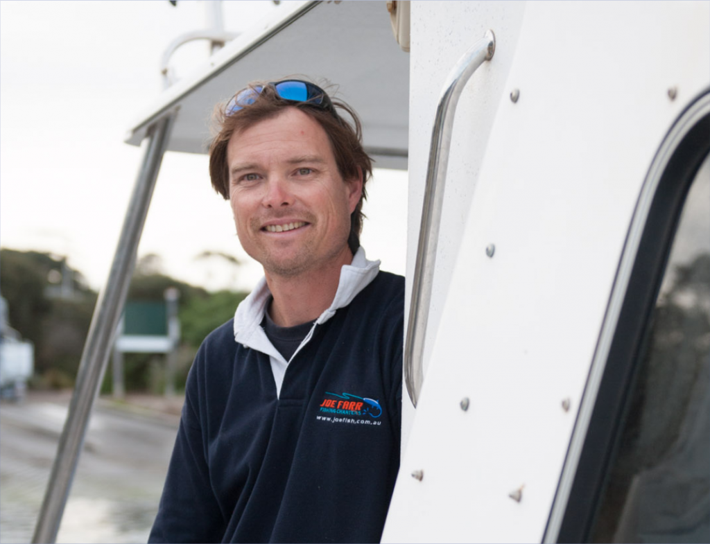 Skipper Joe Farr smiles at the camera from his charter boat Seamphony, wearing a Joe Farr Fishing Charters boating shirt with the Joe Farr Fishing Charters logo in orange and blue