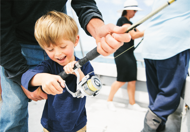 A child smiles and reels in a whiting as someone holds the fishing rod so he can wind it. Is it a snapper, whiting or flathead? He will soon catch his very first fish!