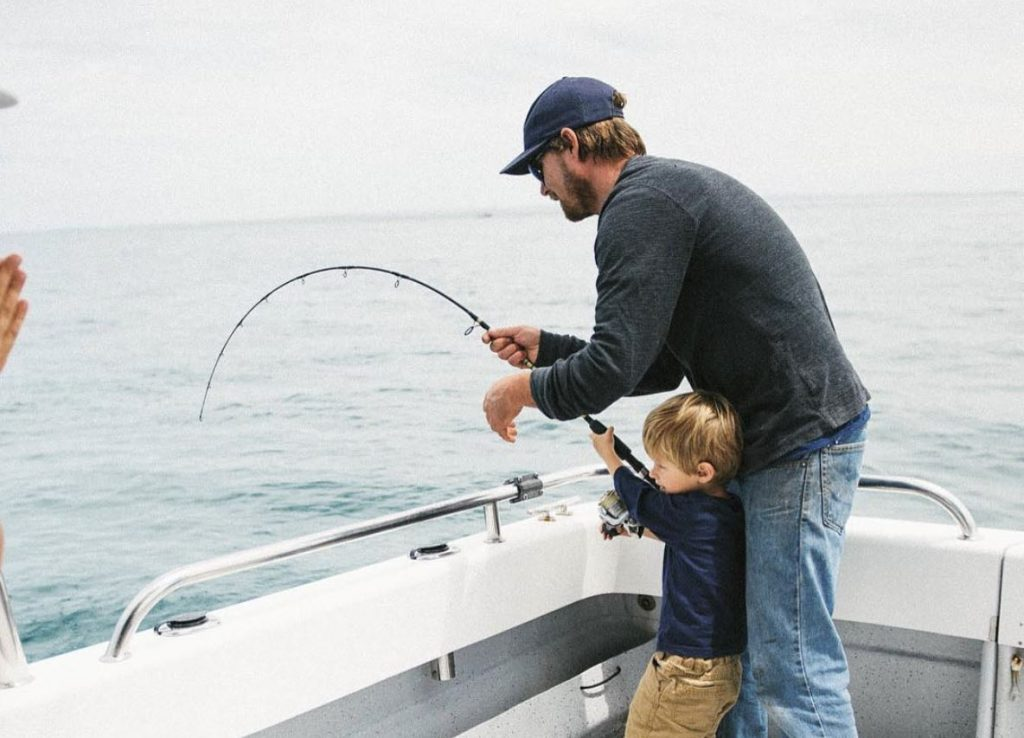 Joe Farr on a family fishing trip helping a young kid reel in a fish aboard his charter boat, which departs Blairgowrie (nearby Sorrento) on the Mornington Peninsula